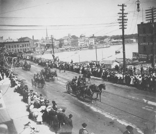 President Roosevelt leaving the dedication ceremony to return to the railroad station. In the background are Memorial Hall, the recently completed Carnegie Library and the excursion boat Illinois.