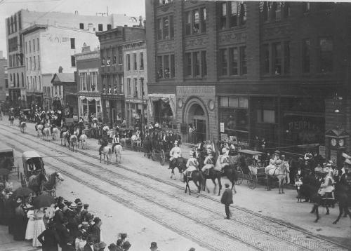 A parade passes in front of the Brown Building, 19th Century.