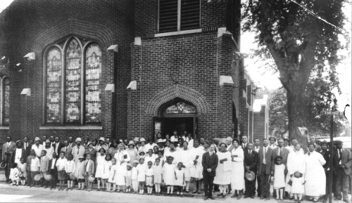 Photo of the congregation in the 1920s in front of the church at Elm and Winnebago.