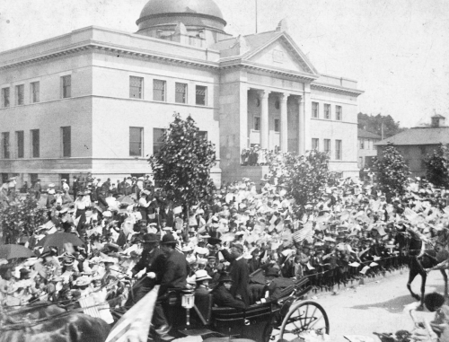 President Roosevelt standing in his carriage as he arrives at Memorial Hall. Behind him is the Carnegie Library.